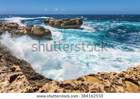 Surging waves break on the rocky shore of Dwejra bay in Gozo, Malta.