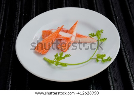 Surimi on a black plate decorated with parsley. - stock photo