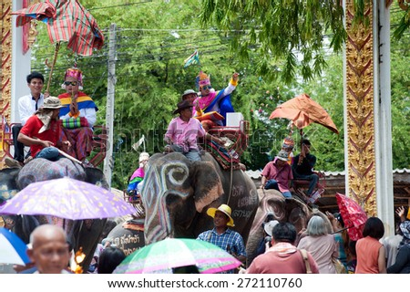 SURIN,THAILAND-MAY 23 : Ordination Parade on Elephant�s Back Festival is when elephants parade and carry Novice monk on their backs at  Wat Chang Sawang to Moon river on May 23,2013 in Surin,Thailand. - stock photo