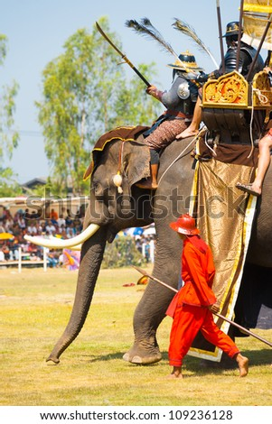 SURIN, THAILAND - NOVEMBER 20: Soldiers and king ride an elephant during the Siamese Burmese war reenactment at the Surin Elephant Roundup on November 20, 2010 in Surin, Thailand - stock photo