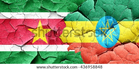 Suriname flag with Ethiopia flag on a grunge cracked wall - stock photo