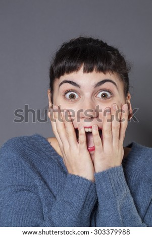 surprise and success concept - cheerful 20s woman wearing a blue winter sweater expressing herself with both hands on face,laughing for surprise and happiness - stock photo