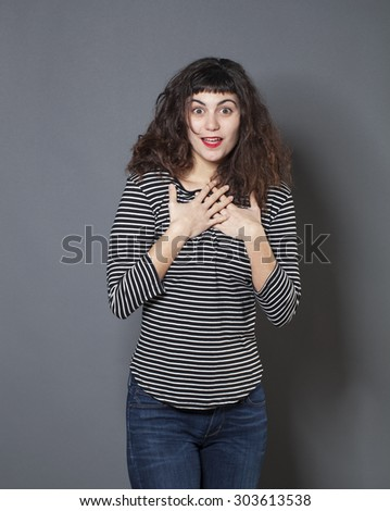 surprise and success concept - cute 20s woman wearing a striped sweater expressing surprise with both hands on her heart and face - stock photo