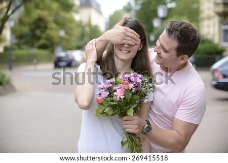 Surprise: Boyfriend with bouquet of flowers holding his  hands over his girlfriend�´s eyes - stock photo