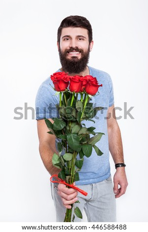 Surprise for her. Handsome young man giving a flower to you while standing against white background