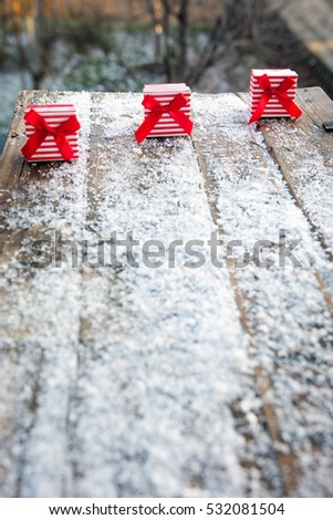 Surprise gifts with red ribbon left outside in snow