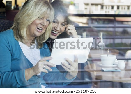Surprise mature women with mouth open looking at the digital tablet while sitting in the coffee shop. Shot through the window.  - stock photo