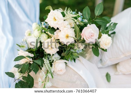 surprise, present, floral design concept. marvelous bouquet composed of various flowers, few kinds of roses, and brunches of rosebush, it placed on the pillow in linen pillowcase