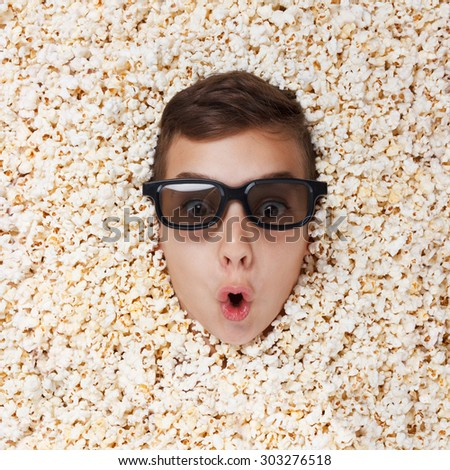 Surprise young boy in stereo glasses watching a movie from popcorn - stock photo