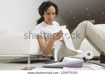 Surprised African American woman calculating her domestic expenses at home - stock photo