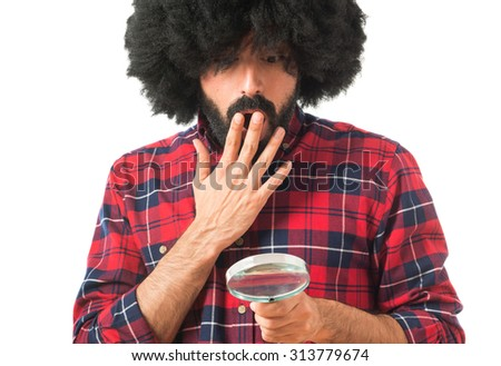 Surprised afro man with magnifying glass  - stock photo