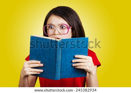 Surprised,Amazed cute little schoolgirl  with a open book on her head, isolated over yellow background.  - stock photo