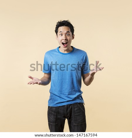 Surprised and amazed looking Asian man standing against cream background. - stock photo