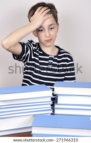 Surprised and astonished young boy holding his forehead with one hand and sitting at the table with books wondering how much he has to read - stock photo