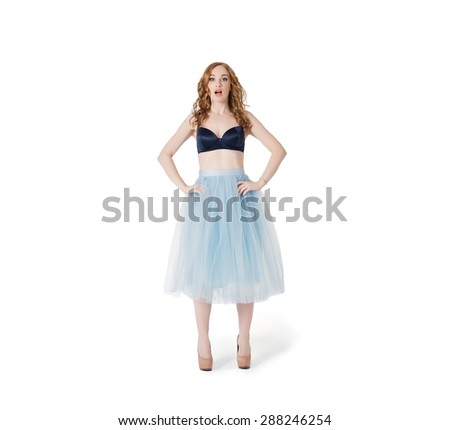 Surprised and confused Yang Red Hair Fashion Woman in underwear and lush skirt isolated on white background. Empty wardrobe problem - stock photo