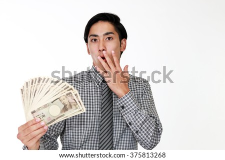 Surprised Asian businessman with money - stock photo