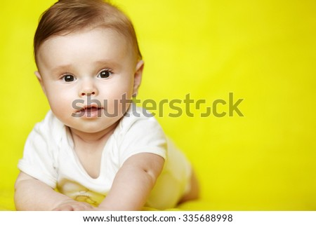 Surprised baby boy on his stomach looking to camera on yellow background. Cute infant kid over bright background. - stock photo