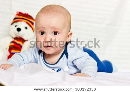 Surprised baby boy portrait lying on bed - stock photo