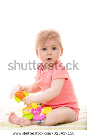 Surprised baby girl playing with  colorful flower toy  - stock photo