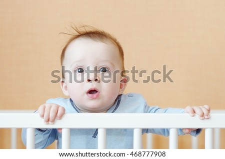 surprised baby in white bed