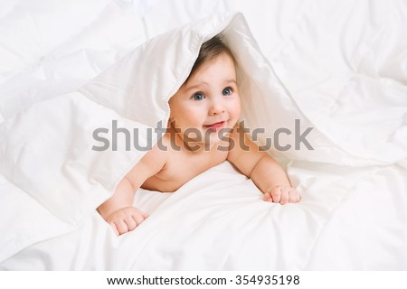 Surprised Baby lies on the bed under the blanket