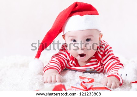 Surprised baby with presents and red cap