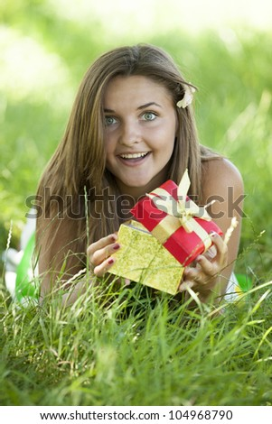 Surprised beautiful teen girl with gift in the park at green grass.