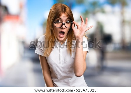 Surprised Beautiful young girl with glasses on unfocused background