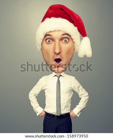 surprised bighead man in santa hat over grey background