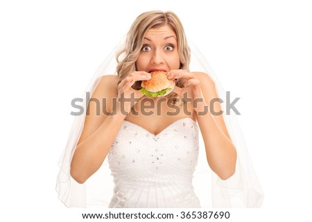 Surprised blond bride eating a sandwich and looking at the camera isolated on white background - stock photo