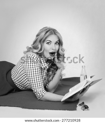 surprised blond woman reading a book lying on a plaid