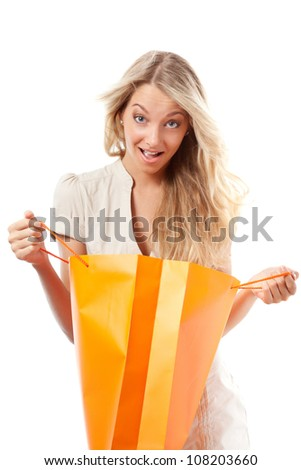 surprised blonde woman holding opened shopping bag - stock photo