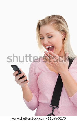 Surprised blonde woman looking at her mobile phone against a white background - stock photo