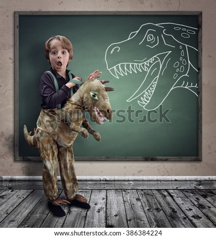 Surprised boy dressed in fancy dress as a dinosaur with chalk tyrannosaurus rex on blackboard concept for education, history, science and imagination - stock photo
