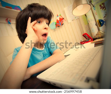 Surprised boy looking at a computer monitor, distance learning. instagram image retro style - stock photo