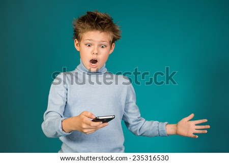 Surprised boy playing games on smartphone on blue background.  - stock photo