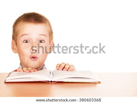 Surprised boy sitting with a book at a table isolated on white background