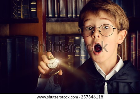 Surprised boy stands with watch in the library with many old books. Fairy tales. Vintage style. - stock photo
