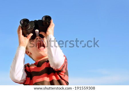 Surprised boy with binoculars against blue sky - stock photo