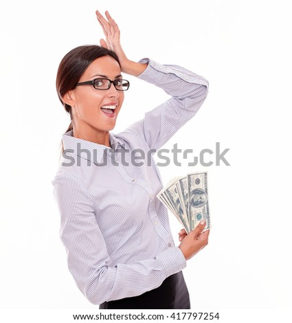 Surprised brunette businesswoman showing money and holding with a satisfied gesture of her hand to her head while wearing her straight hair back in a button down shirt on a white background - stock photo