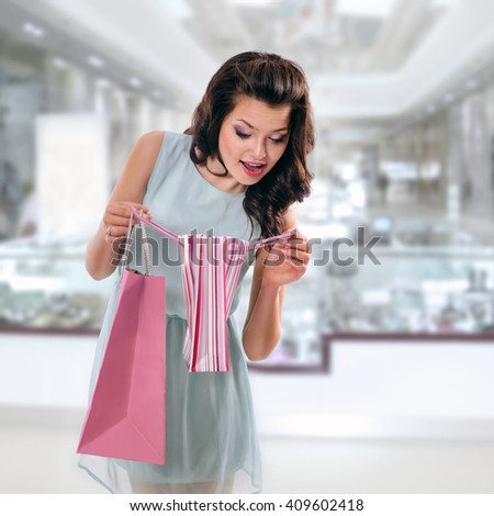 surprised brunette girl in blue dress with shopping bags in  store - stock photo
