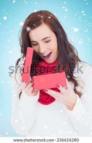 Surprised brunette opening christmas gift against blue background with vignette - stock photo
