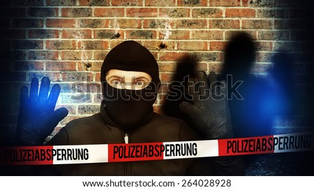 Surprised burglar stopped because of blue police light and take his hands up - stock photo