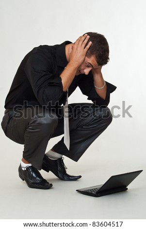 Surprised business man looking laptop - stock photo