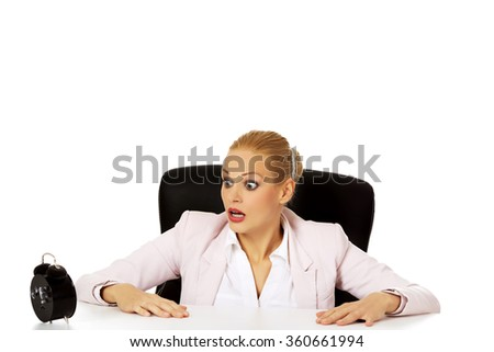 Surprised business woman looking at alarm clock behind the desk - stock photo