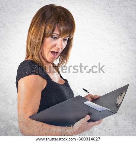 Surprised business woman looking documents over grey background