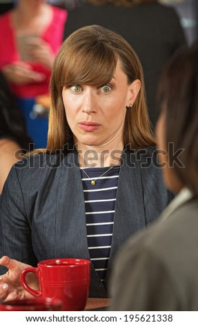 Surprised business woman with wide eyes listening to coworker - stock photo