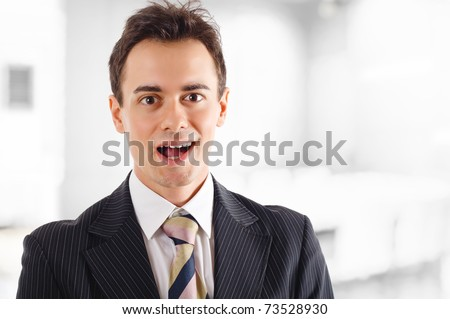 Surprised businessman opening his mouth in an office environment. - stock photo