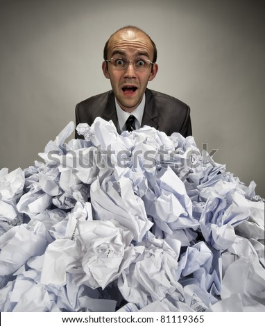 Surprised businessman reaches out from big heap of crumpled papers - stock photo