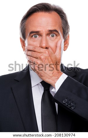Surprised businessman. Surprised mature man in formalwear covering mouth with hand and looking at camera while standing isolated on white background - stock photo